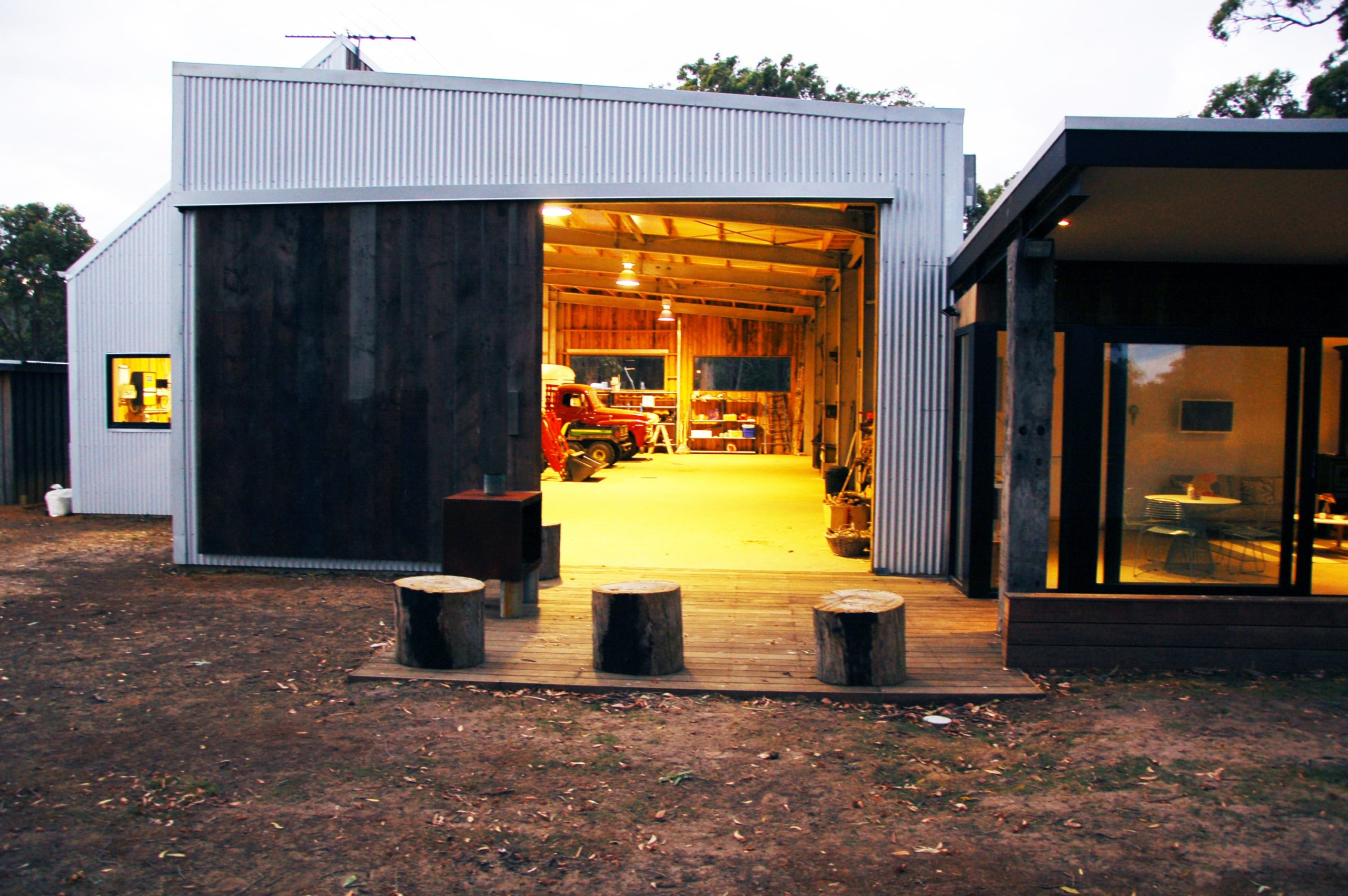 The sitting area at the back of the garage and shed has a wooden deck flooring that leads the way back inside and also to the patio on the side.