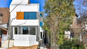 This modern home has white and gray exterior walls complemented by the large glass windows accented with a wooden panel on the side. Here you can also see the side entrance through a long and narrow walkway.