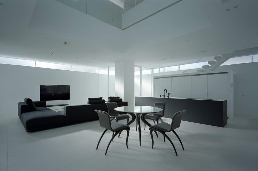 This is a simple dining area in the middle of the great room that also houses the living room and kitchen. It has a modern black dining set that stands out against the white floor, walls and ceiling.