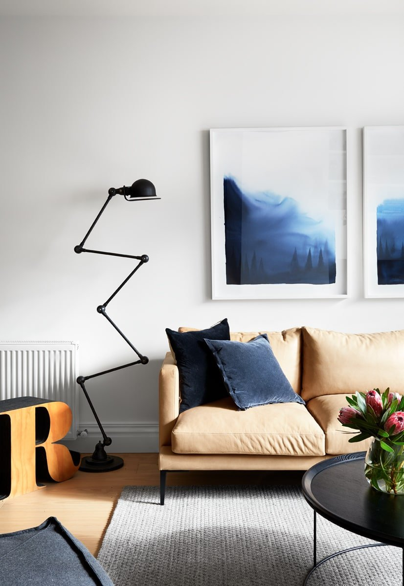A closer look at the living room focuses more on the wall-mounted paintings above the sofa as well as the black modern standing lamp on the side.