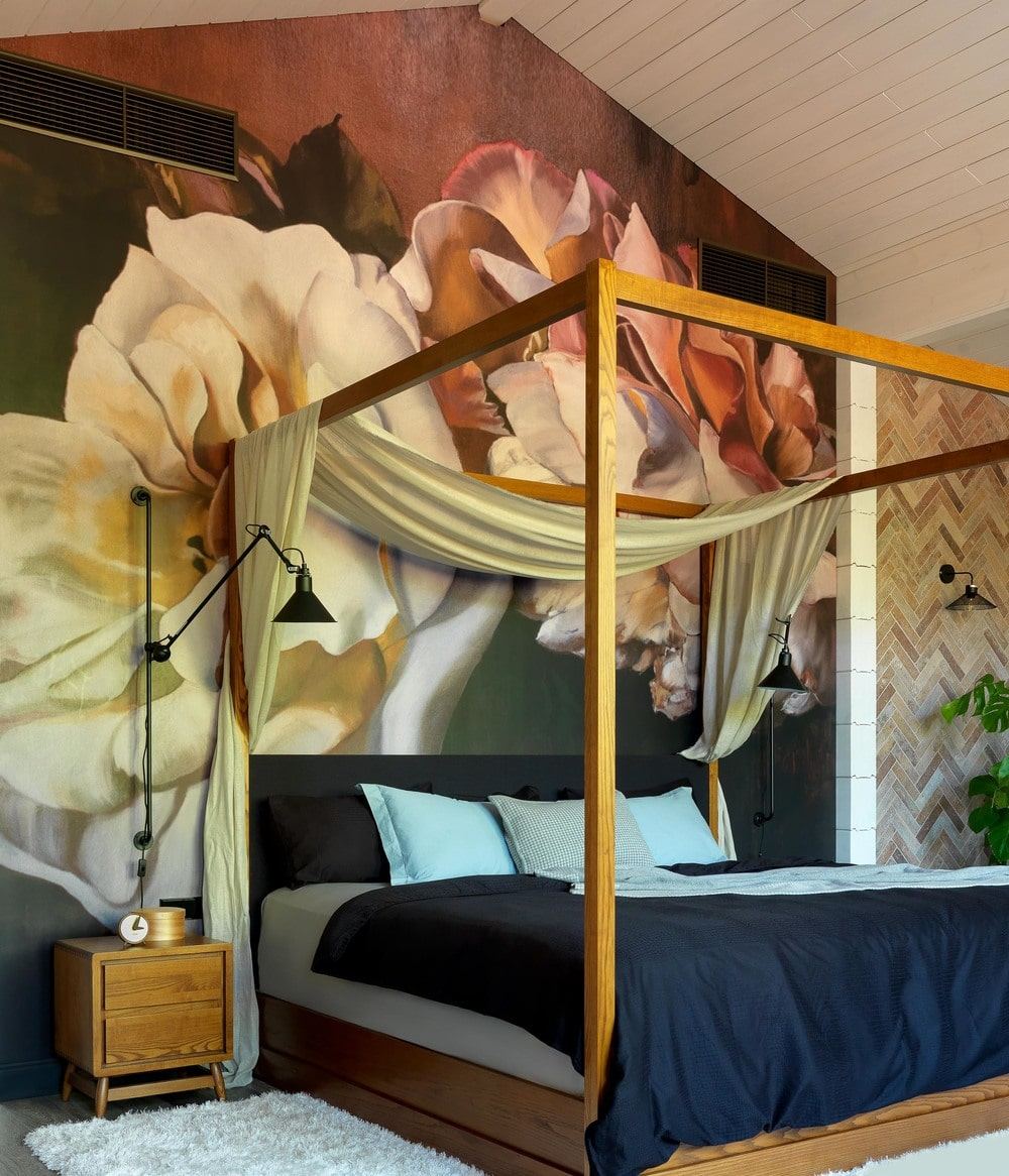 The large colorful mural behind the bed sets the aesthetic of the bedroom. It gives it a colorful and artistic contrast to the neutral tones of the room including the white cathedral ceiling and the curtain of the bed.