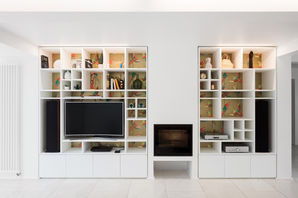 Across from the sofa is this large wooden structure that has built-in shelves and also houses the TV and the fireplace.