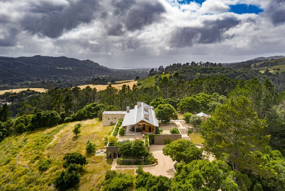 This is the aerial view of the gorgeous house. Here you can appreciate its isolation and the lush landscaping surrounding it with tall trees and rolling hills.