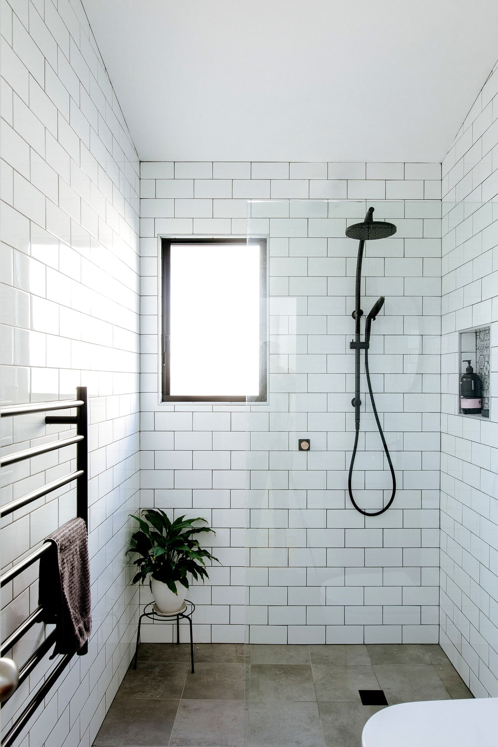 This other bathroom has a glass-enclosed shower area. It has white subway tiles on its walls that contrast well with the black fixtures of the bathroom.