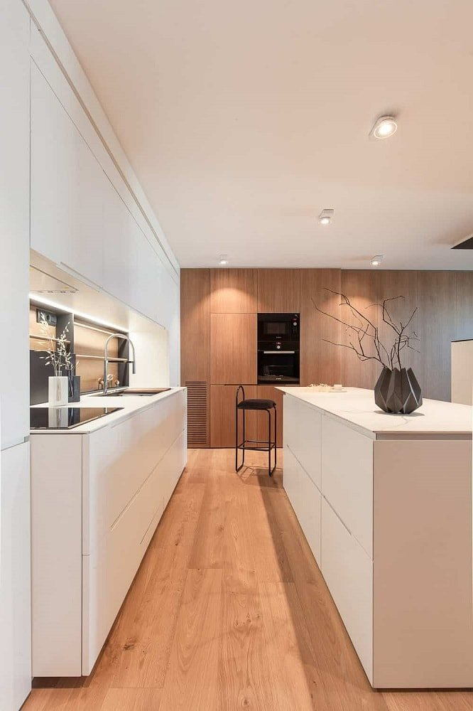 This is the modern long and narrow kitchen with white modern cabinetry matching with its white countertops and the white ceiling. This is complemented by the hardwood flooring and the wooden tone of the wall on the far end.