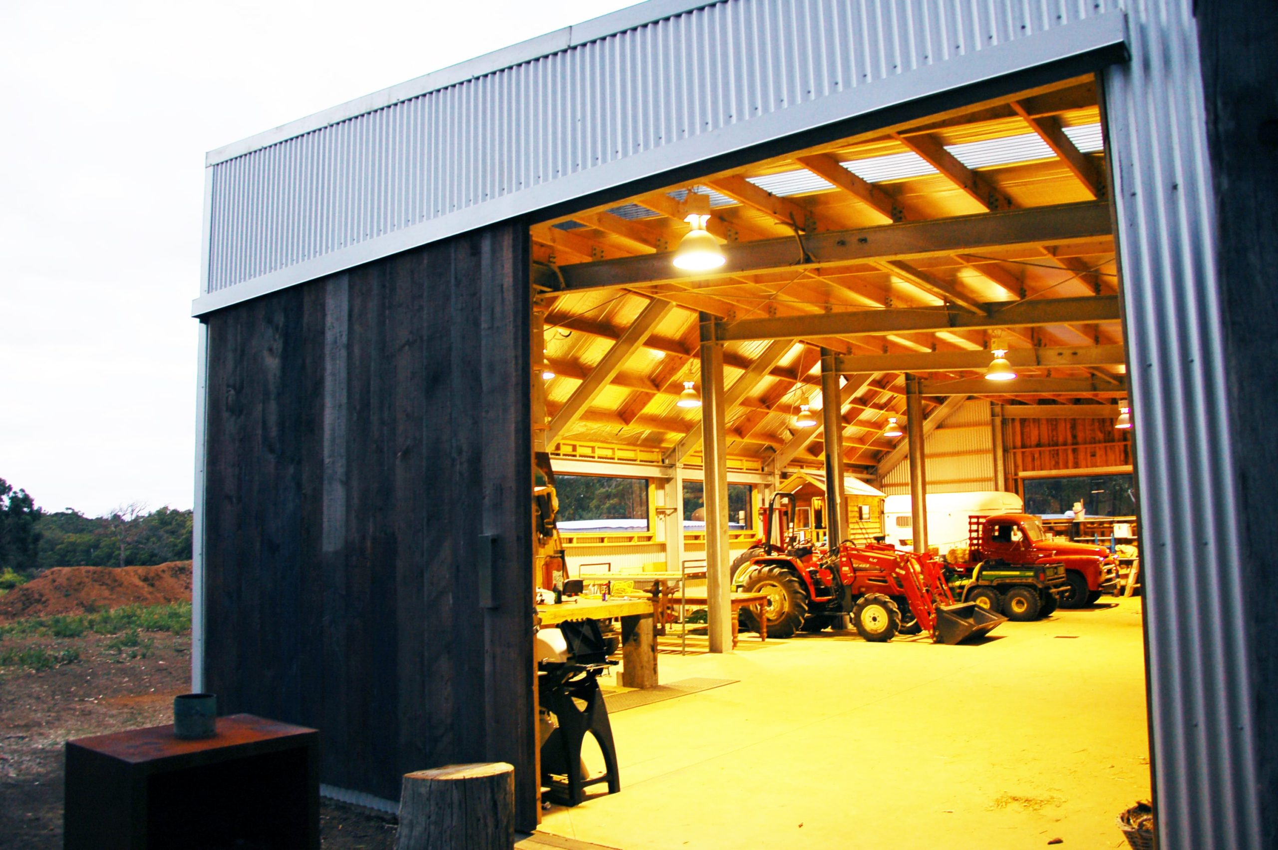 The large shed and garage also has a spacious work area on the side of the parked vehicles. brilliantly lit by the large lighting of the wooden ceiling with exposed beams.