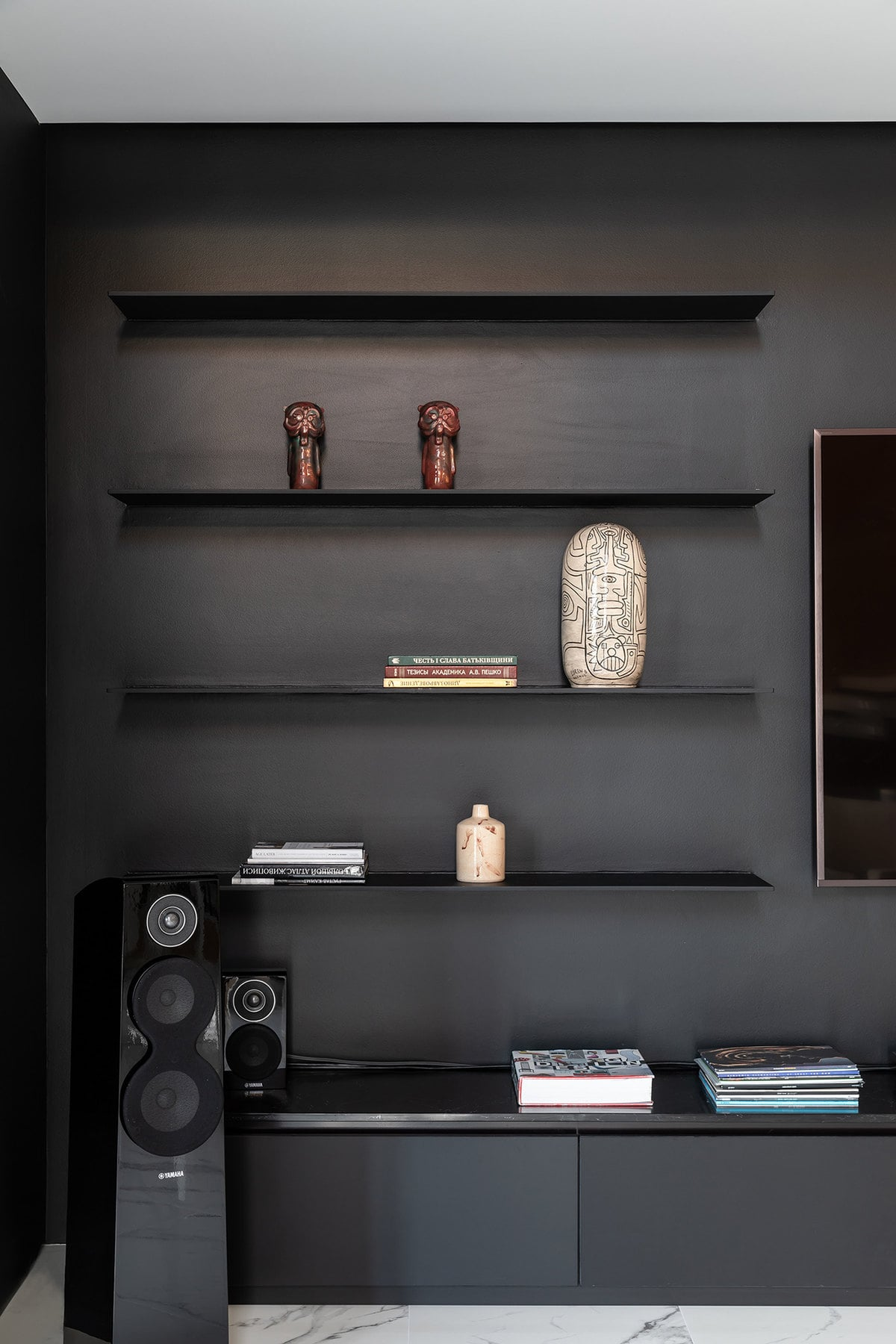 This is a closer look at the black wall and its built-in floating shelves that are perfect for decors beside the wall-mounted TV.