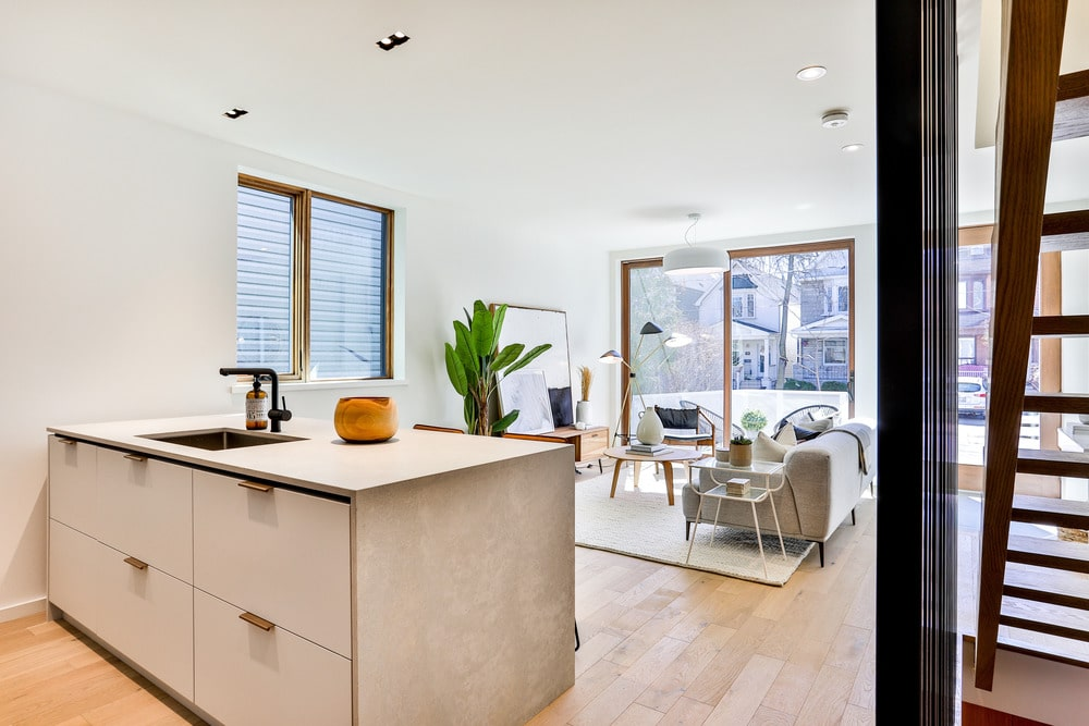 This view shows the proximity of the wooden kitchen island to the living room on the far side. This kitchen island matches well with the light hardwood flooring contrasted by the sink.