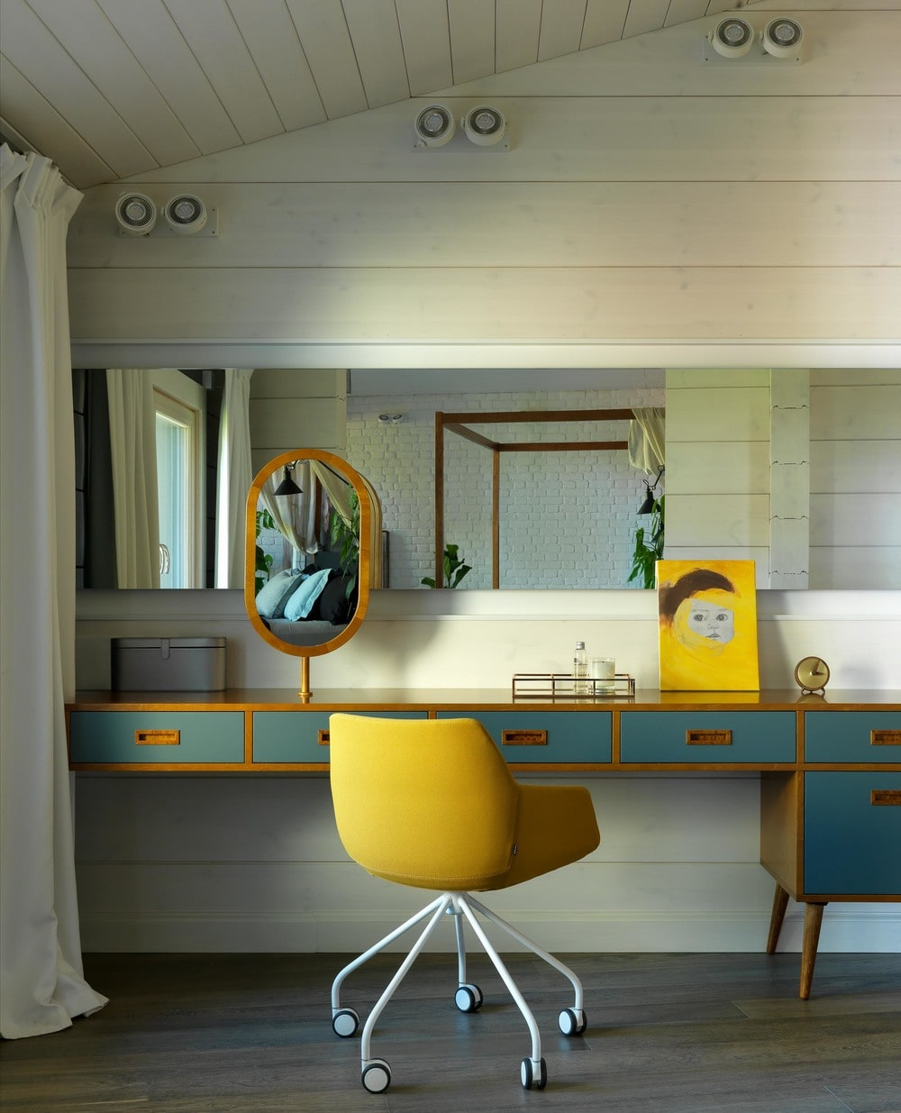 Across from the bed is this charming wooden vanity with built-in drawers painted green to stand out against the white shiplap wall with a large wall-mounted mirror and a yellow swivel chair.