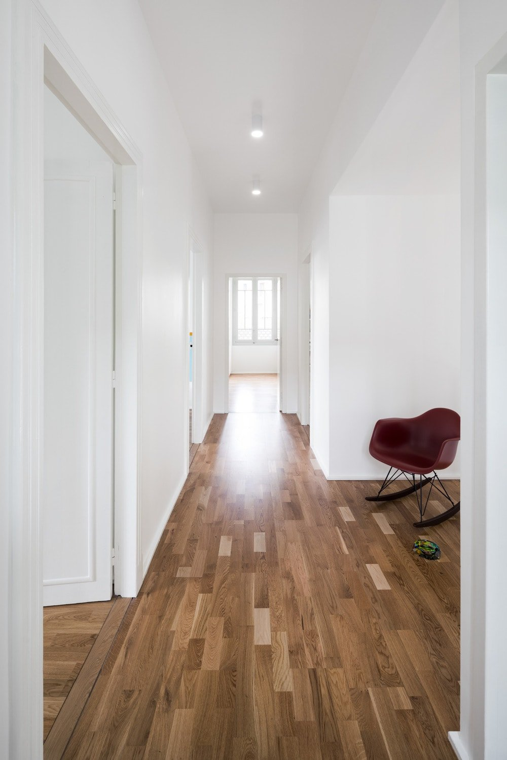 This is the second-floor hallway with a dark hardwood flooring contrasted by the bright white walls and ceiling. Here you can see that the doors of the room blend well with the white walls.