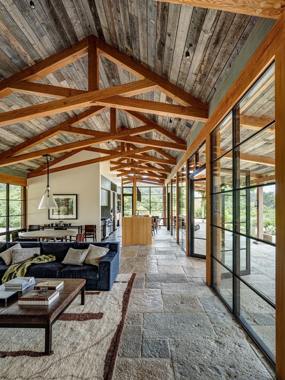 This is the great room that houses the living room, dining area and the kitchen under the same tall cathedral ceiling with exposed beams that stand out against the wooden ceiling.