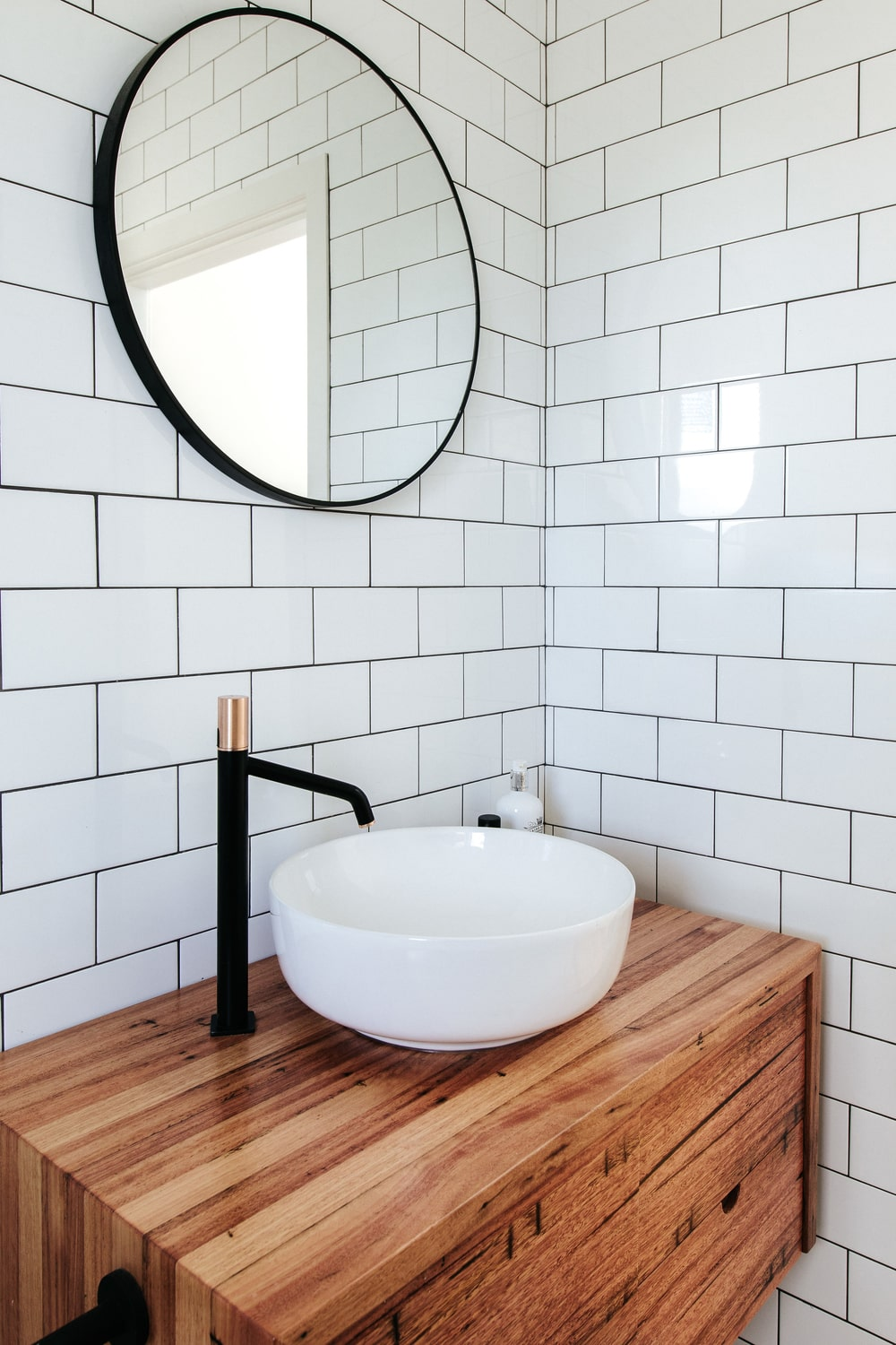This is the lovely wooden vanity of the bathroom contrasted by its freestanding white porcelain bowl sink.This pairs well with the white subway tiles of the walls.