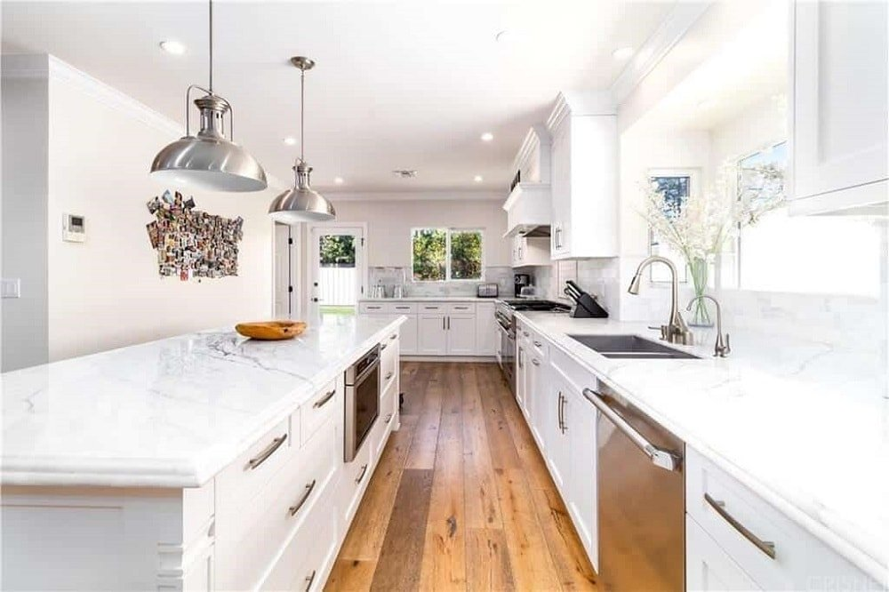 The white countertop of the kitchen island is topped with a couple of stainless steel pendant lights that match those modern appliances housed by the white cabinetry that is complemented by the hardwood flooring in this long and narrow kitchen.