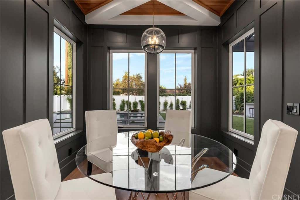 This is an intimate dining area with a small glass-top dining table surrounded by white cushioned chairs. These chairs stand outa gainst the matte black walls with large windows.