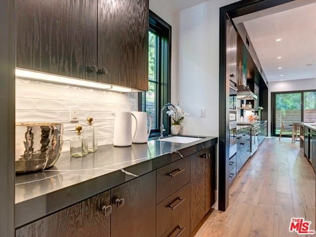 This view of the kitchen showcases its lovely long and narrow design with a row of black cabinetry lining the wall topped iwth black marble countertops that contrasts the bright backsplash illuminated by the lighting of the floating cabinets.