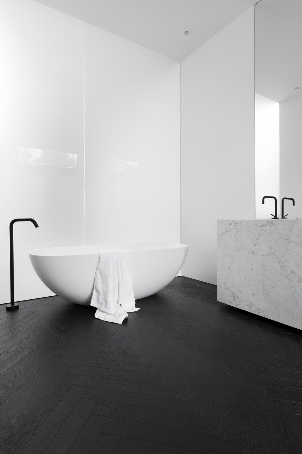 The primary bathroom has a black flooring that is contrasted by the white porcelain freestanding bathtub that blends with the white wall and white marble vanity.
