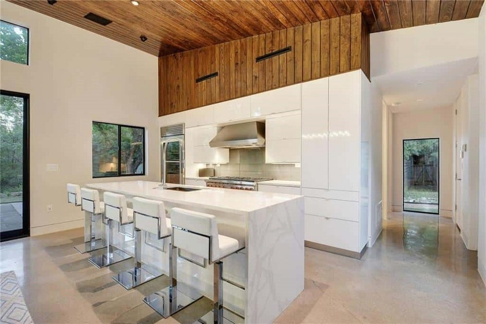 The modern white cabinetry of the long and narrow kitchen is a perfect match for the white countertops and the white cushioned stools of the breakfast bar. These are then complemented by the hardwood flooring and the wooden shiplap ceiling.
