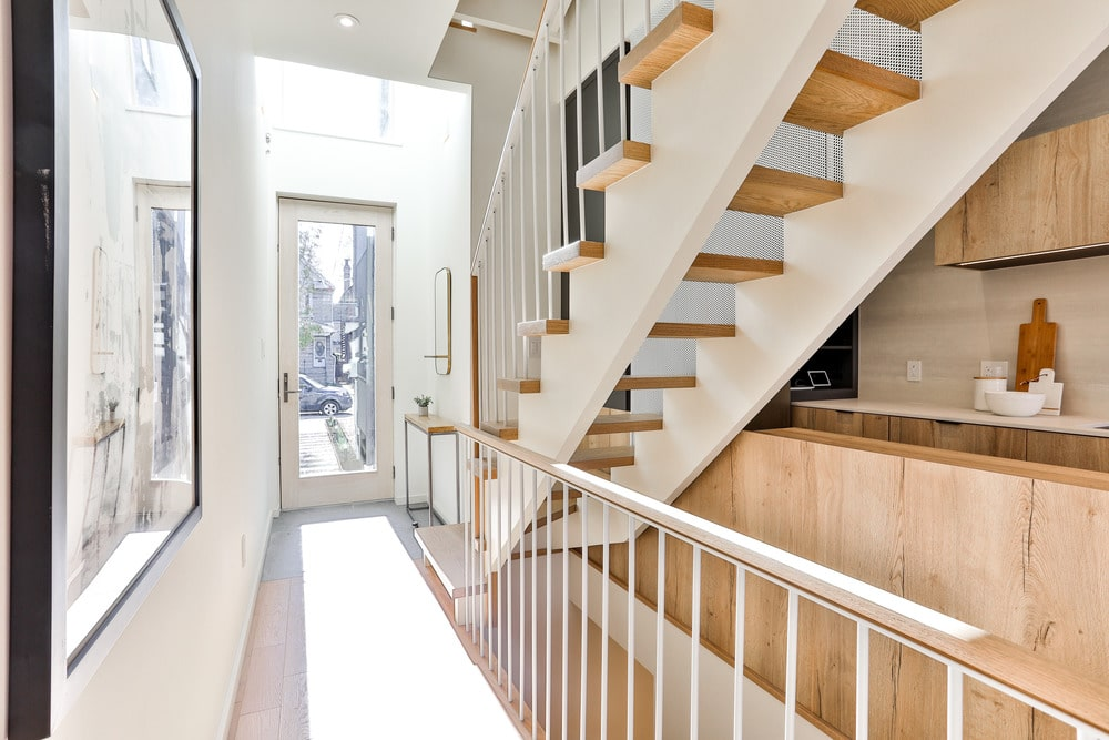 This hallway leads to the back door with a large glass panel. There is a small console table on the side and you can also see a bit of the kitchen from this vantage point.