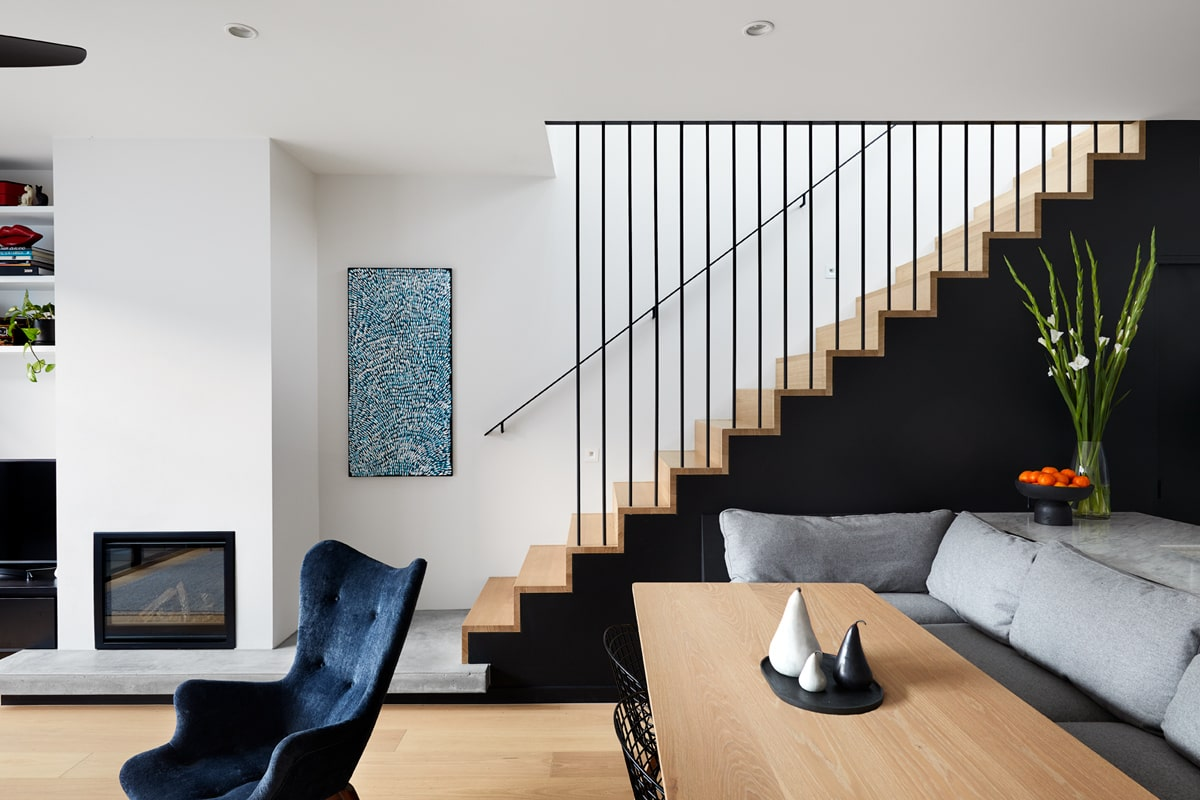 A closer inspection of the dining area shows the bench is actually attached to the kitchen island of the kitchen behind it. You can also appreciate the black wall of the staircase from this angle.