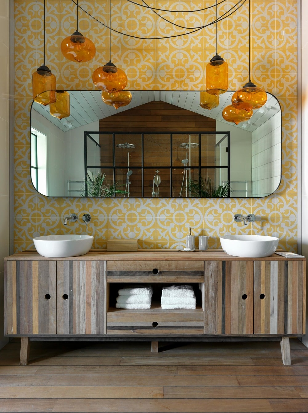 This is the bathroom with a gorgeous vanity area that has two sinks and a large wall mirror. These are then complemented by the patterned yellow tiles of the wall to match the set of lovely yellow pendant lights.