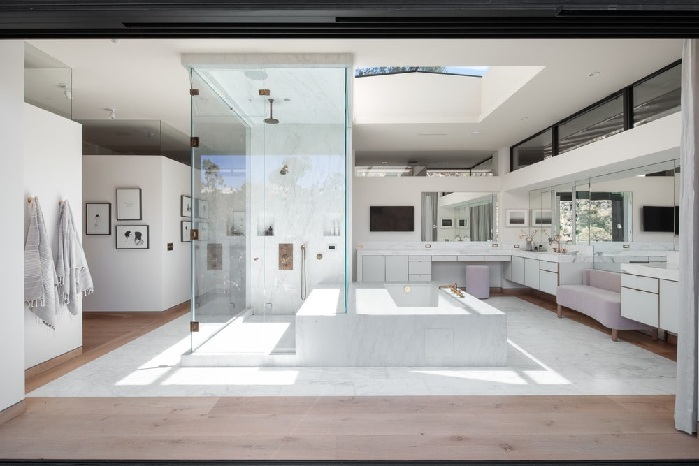 The bright and white spacious primary bathroom has a large bathtub in the middle under the bright skylight. On the side of the bathtub is the glass-enclosed shower area with the same bright tone as the rest of the bathroom.