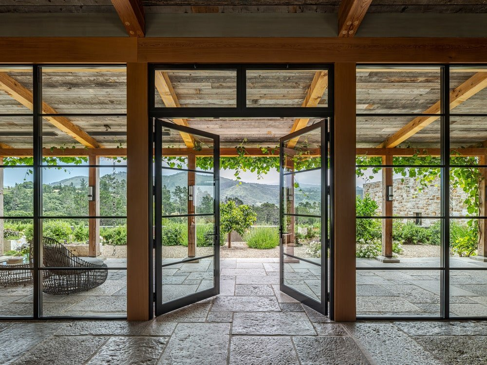 The covered patio beyond the glass walls has a beamed ceiling wupported by a row of wooden columns. This area is accessible through a set of large glass doors.