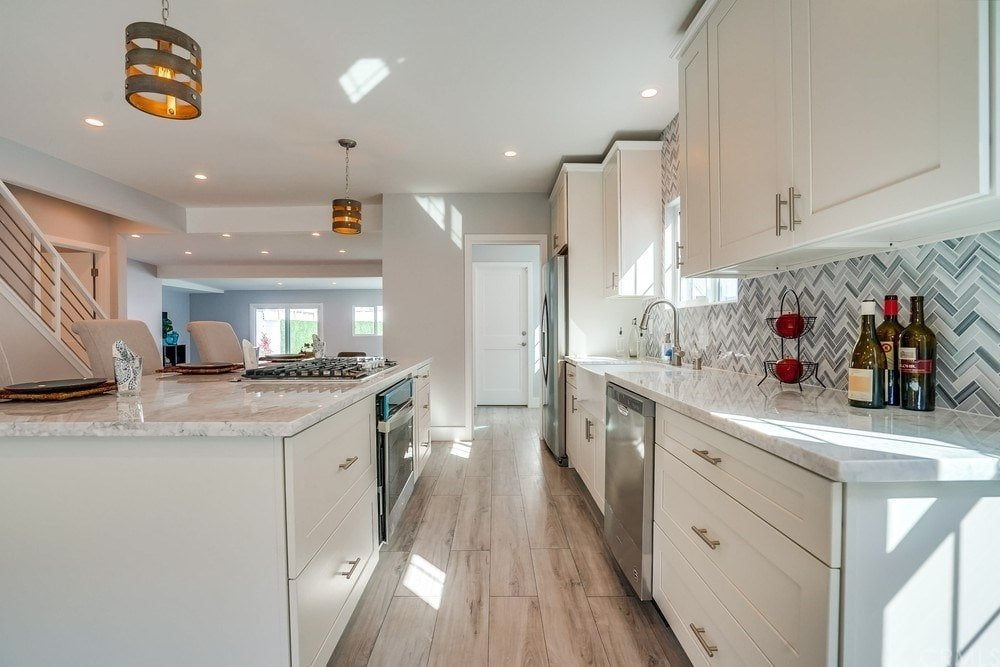 This is a simple yet elegant kitchen with classic white cabinetry to house the stainless steel appliances complemented by the hardwood flooring and the decorative pendant lights over the kitchen island.