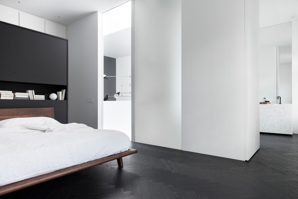 The beautiful primary bedroom has a wooden platform bed that stands out against the black floor, white walls and white ceiling. This view also shows the doorway leading to the bathroom.
