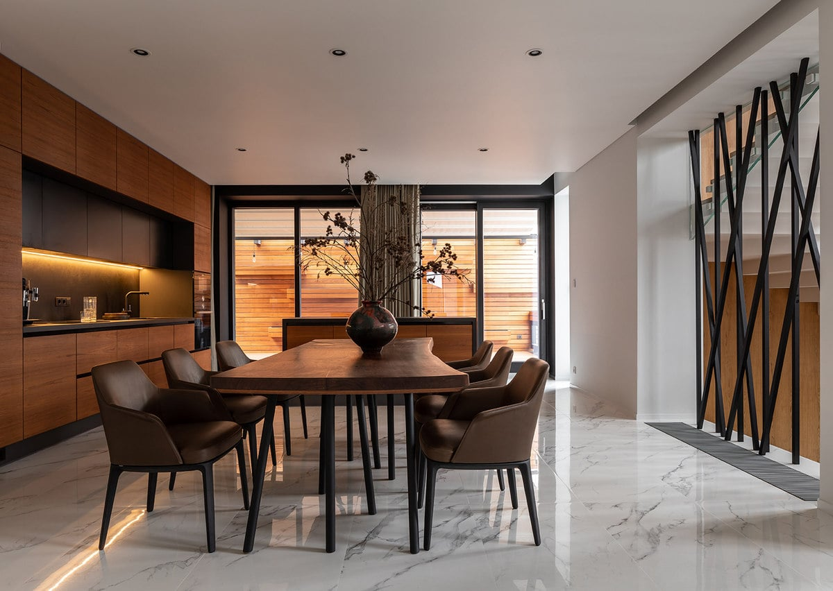 The white marble flooring of the kitchen and dining area matches perfectly with the white ceiling with recessed lights. These are then illuminated by the large glass windows on the far side.