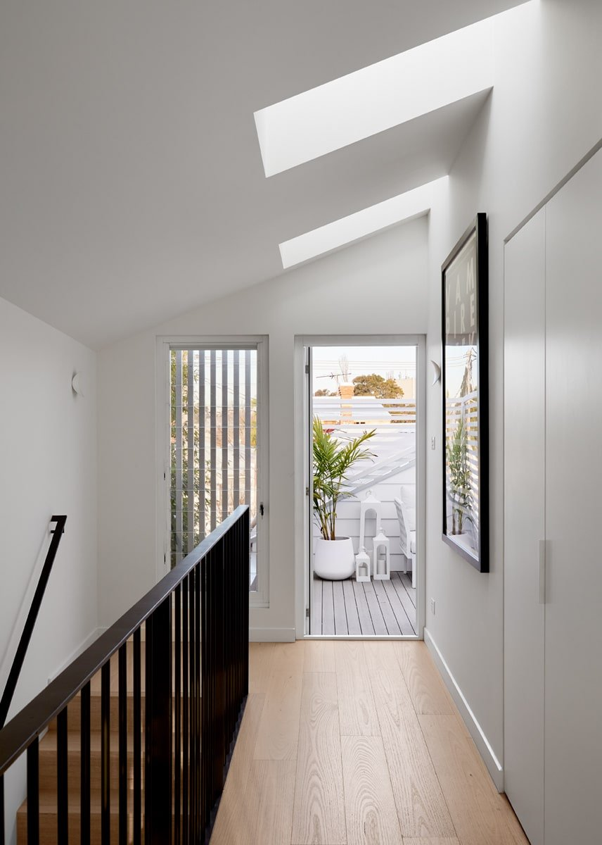 The second floor landing has gorgeous white walls and a white shed ceiling with skylights that bring in natural lighting. This also leads to the balcony on the far end.