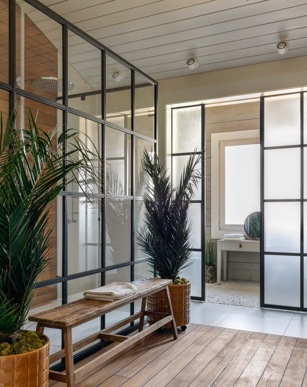 Across from the vanity area is a rustic wooden bench flanked by potted plants against the glass wall of the shower area. This has lovely black frames to stand out against the bright walls of the bathroom.