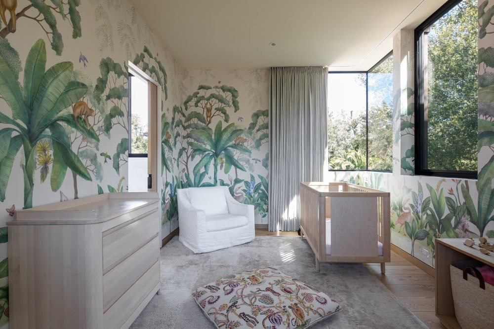 This is a charming nursery with gorgeous colorful murals dominating the walls with depictions of plants and trees. This gives a nice splash of color to the neutral tones of the crib, armchair and dresser.