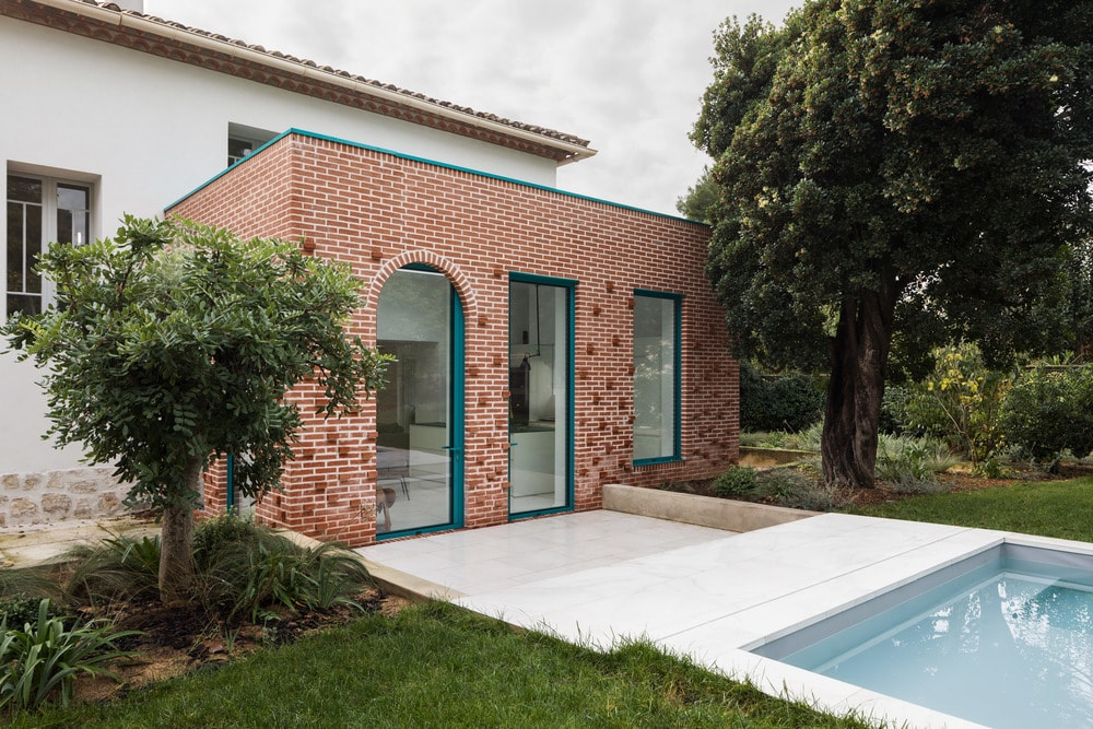 The lovely brick section of the house is adroned with green frames to its door and windows to match the lush green landscape of the backyard with tall trees and a grass lawn.