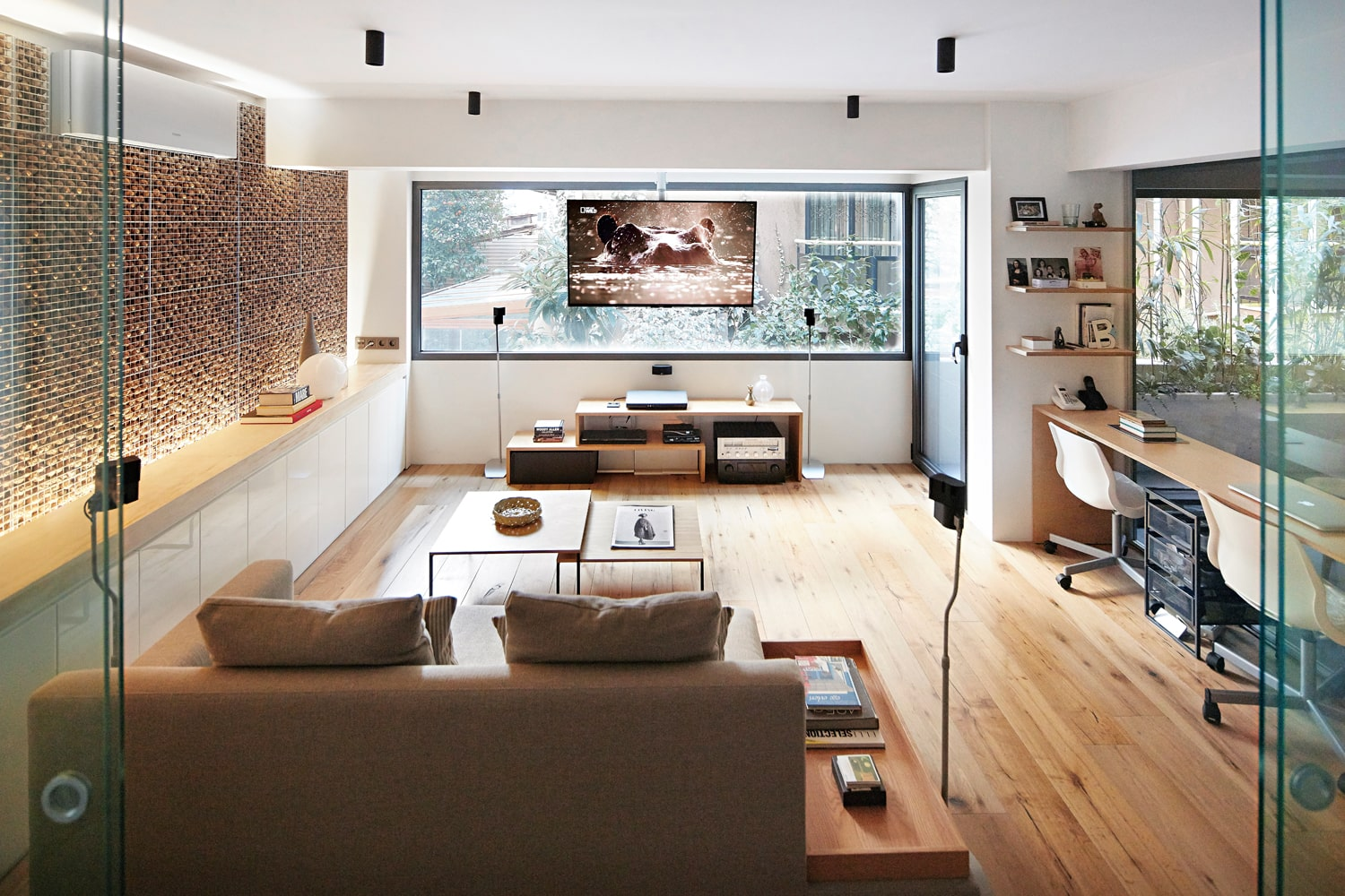 On the opposite of this walnut wall is a work area that has a long wooden desk that matches the hardwood flooring adorned with a large glass wall.