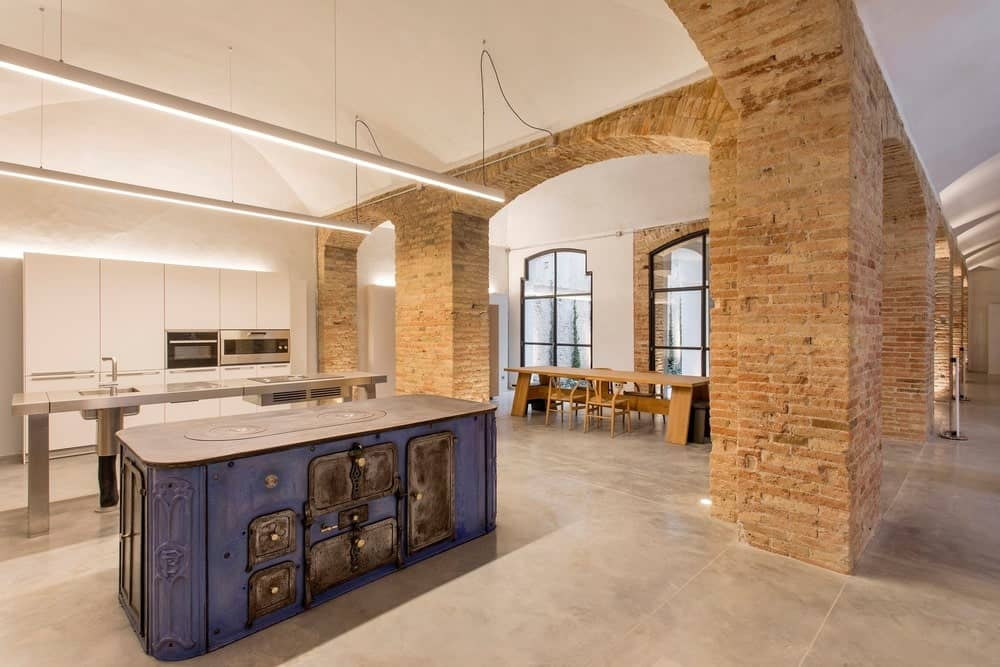 This is a spacious Industrial-style kitchen with a tall arched ceiling complemented by the exposed beams. The large kitchen islands are complemented by the thick red brick arches and columns of the entryway.