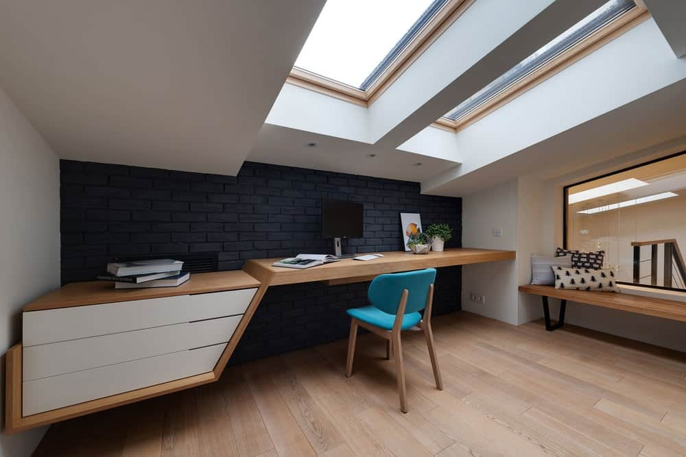 The hardwood flooring matches with the surface of the built-in desk that has white drawers to match the white shed ceiling with skylights. This is then contraste dby the black brick wall of the desk.
