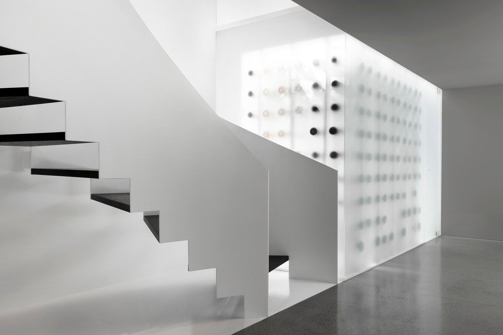 This is the bottom of the stairs that has a large wine cellar enclosed in frosted glass walls giving it a unique look.
