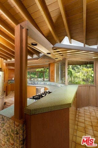 This view of the kitchen showcases its beautiful kitchen peninsula that is connected to the wooden ceiling with exposed beams via a few wooden columns at strategic parts of the kitchen peninsula.