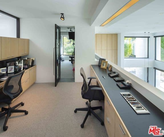 The home office has an indoor balcony that brings in natural lighting for the white walls and ceiling. This matches wellw ith the wooden cabinetry and built-in <a class=