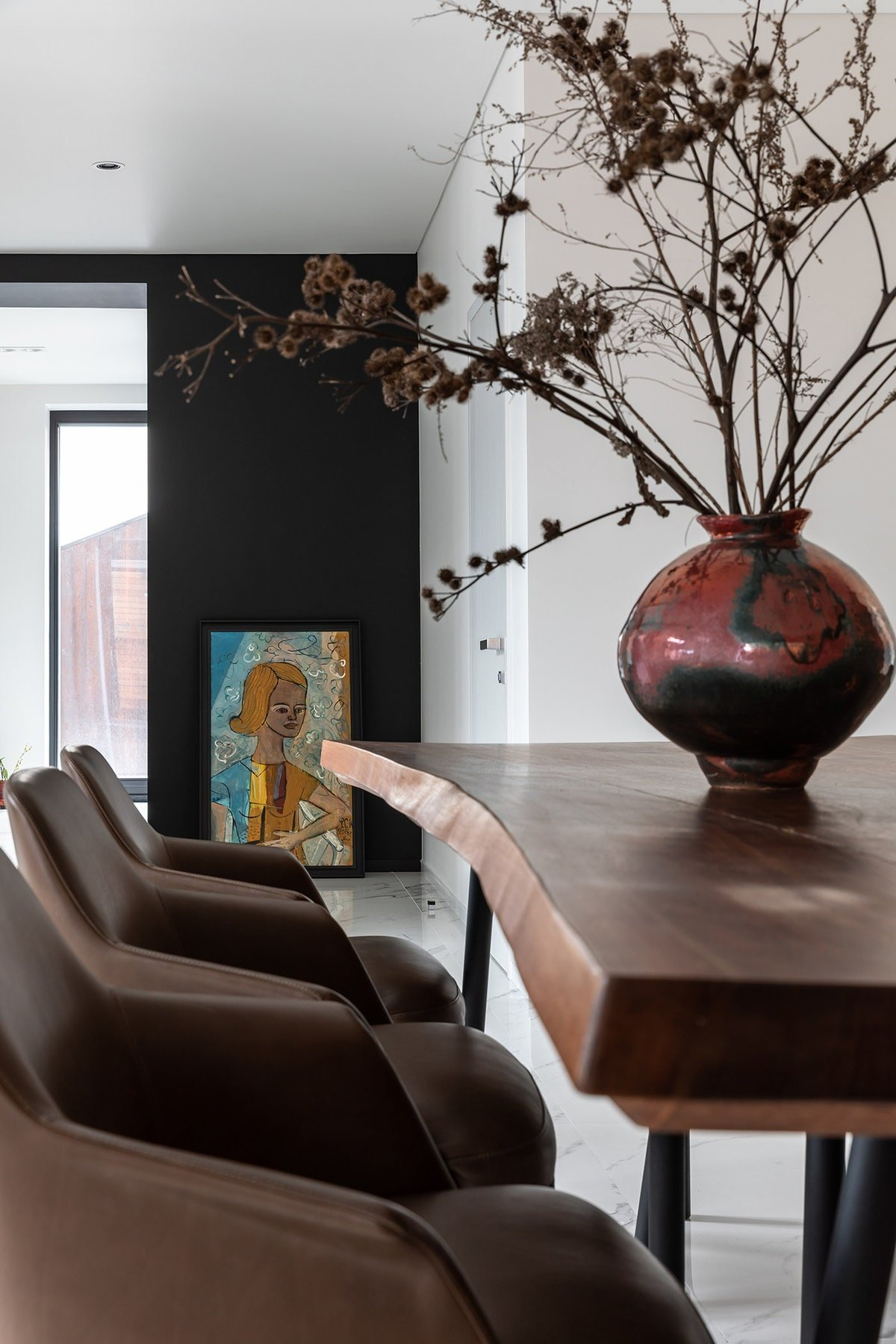 This is a closer look at the dining table that is adorned with a large jar centerpiece. On the far wall is a black panel adorned with a colorful painting leaning on the wall.