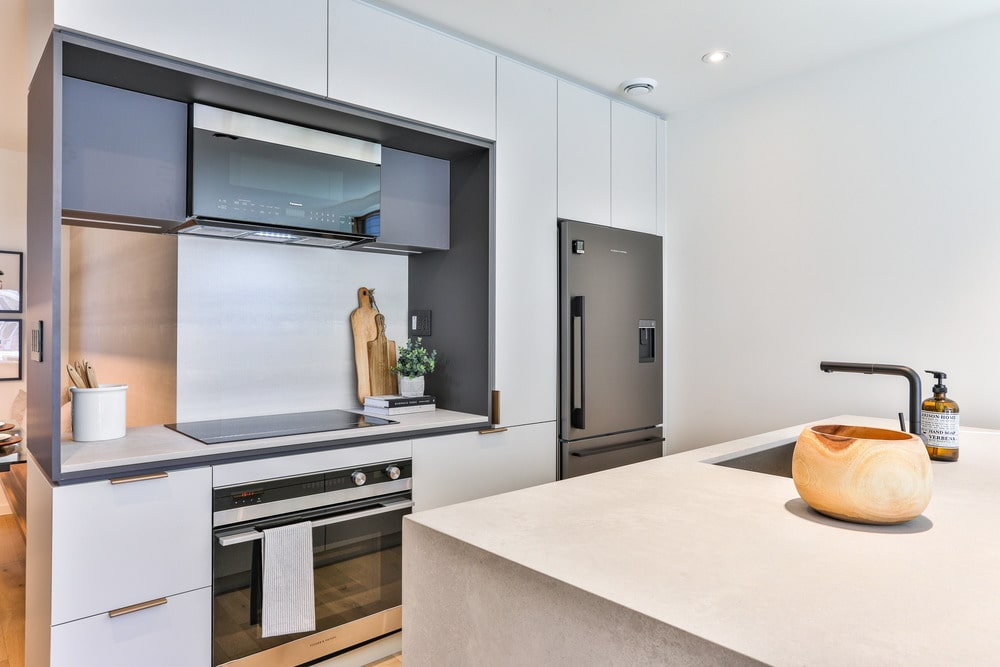 The kitchen has a charming cooking area with a glass top to its modern stove and oven. This is topped with a dark brown wooden vent hood that makes it stand out against the white walls.