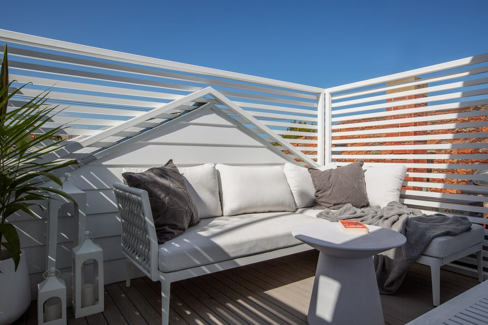 The larger balcony has a white outdoor sofa with cushions paired with a small round side table.