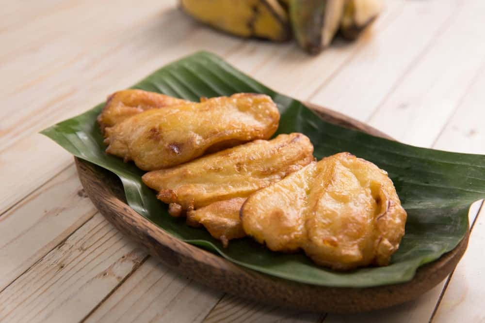 Pieces of freshly fried pisang goreng on a wooden plate.