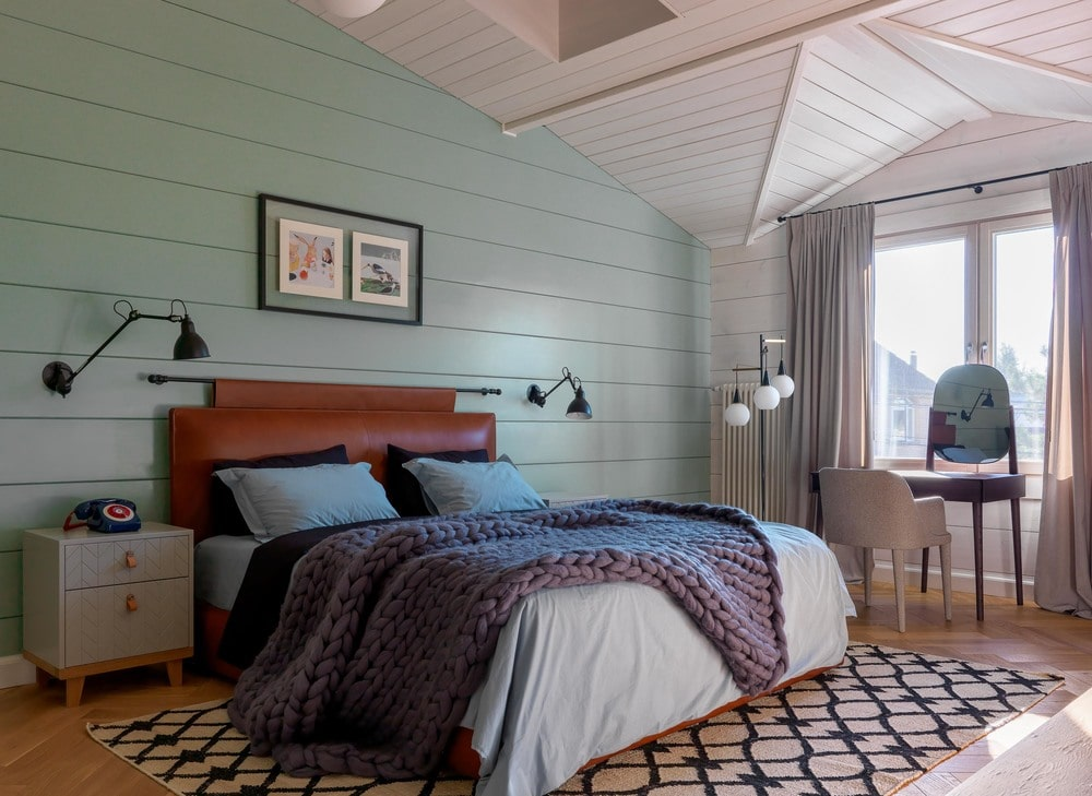 This other bedroom pastel green shiplap wall behind the headboard of the bed. This goes well with the white cathedral ceiling with skylights. Beside the bed is a small vanity area with a wooden table and a tabletop mirror facing the bright window.