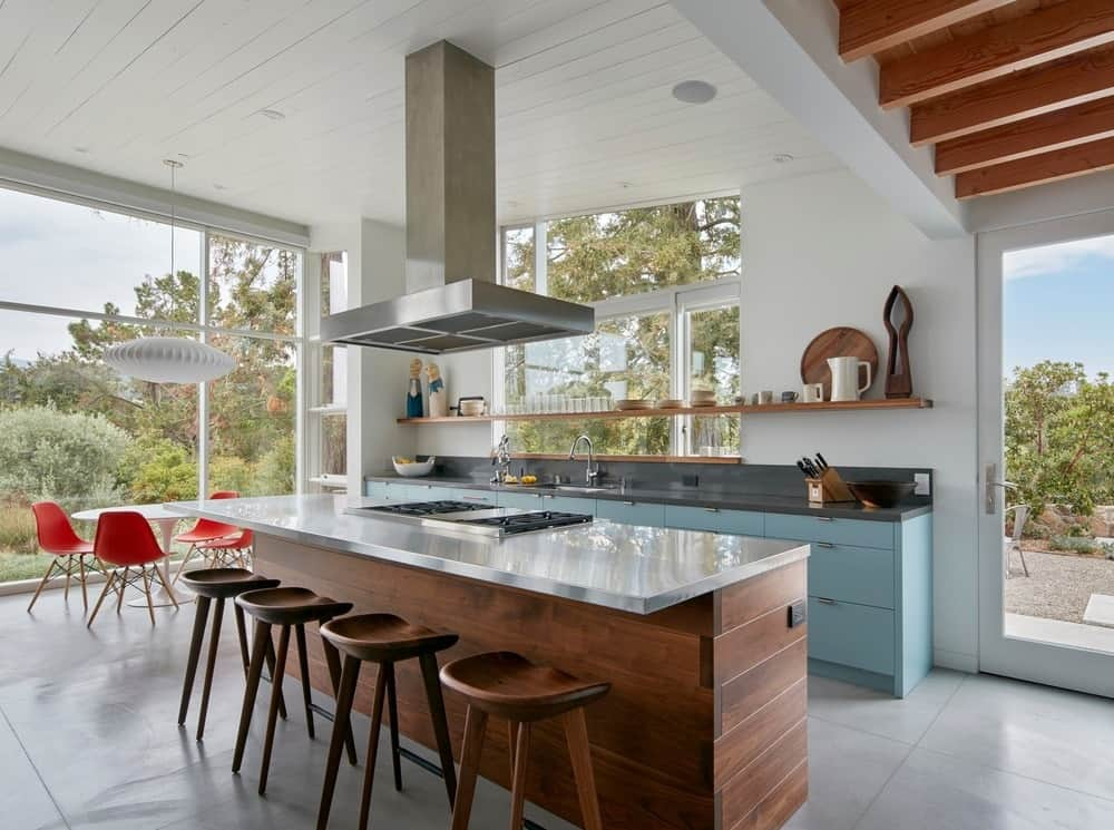 This kitchen has a long kitchen island paired with wooden stools for a breakfast bar. This is topped with a stainless steel vent from the tall white shed ceiling.