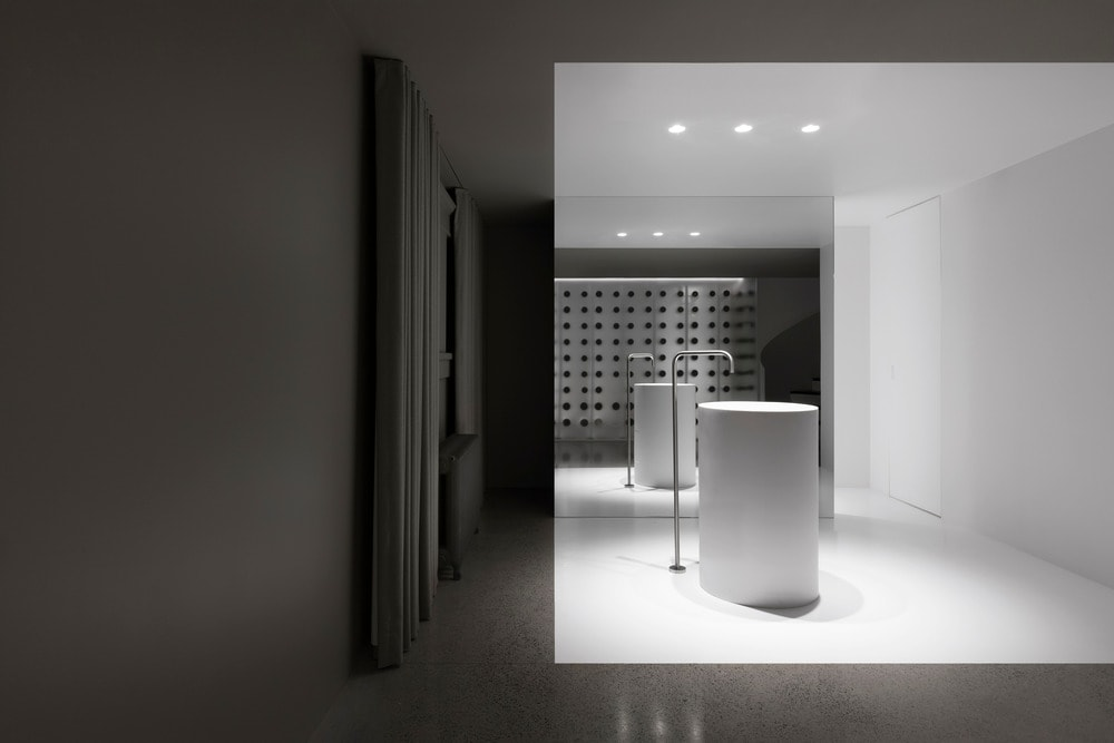 This is a gorgeous power room that evokes an optical illusion with its primaryful placement of tiles and mirrors.