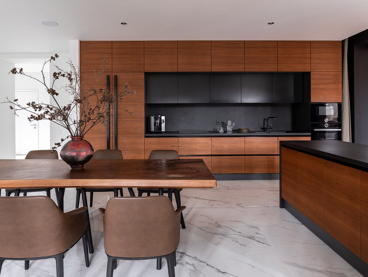 This other view of the dining area shows more of the brown wooden cabinetry of the kitchen. This is accented with a black countertop and backsplash that stands out against the white marble flooring.