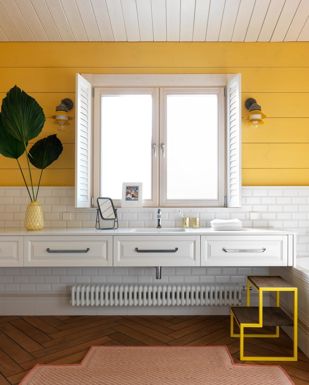 The other bathroom has a sunny yellow shiplap wall to complement the white subway tiles of the backsplash above the white floating vanity with built-in drawers.