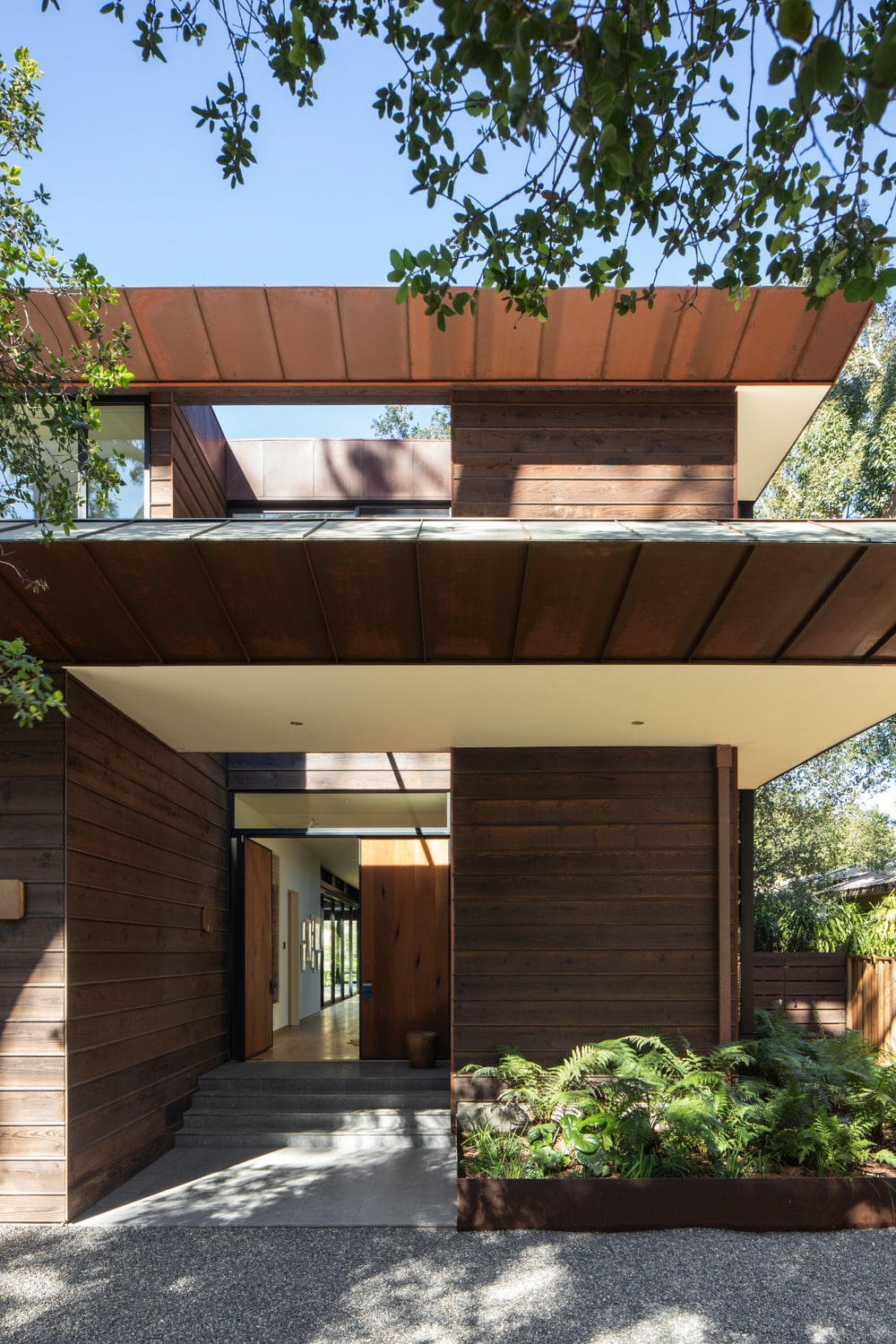 This is a closer look at the main entrance of the house with a wooden main door to match the wooden exterior walls. This area is adorned with lovely planter on the side of the concrete walkway.