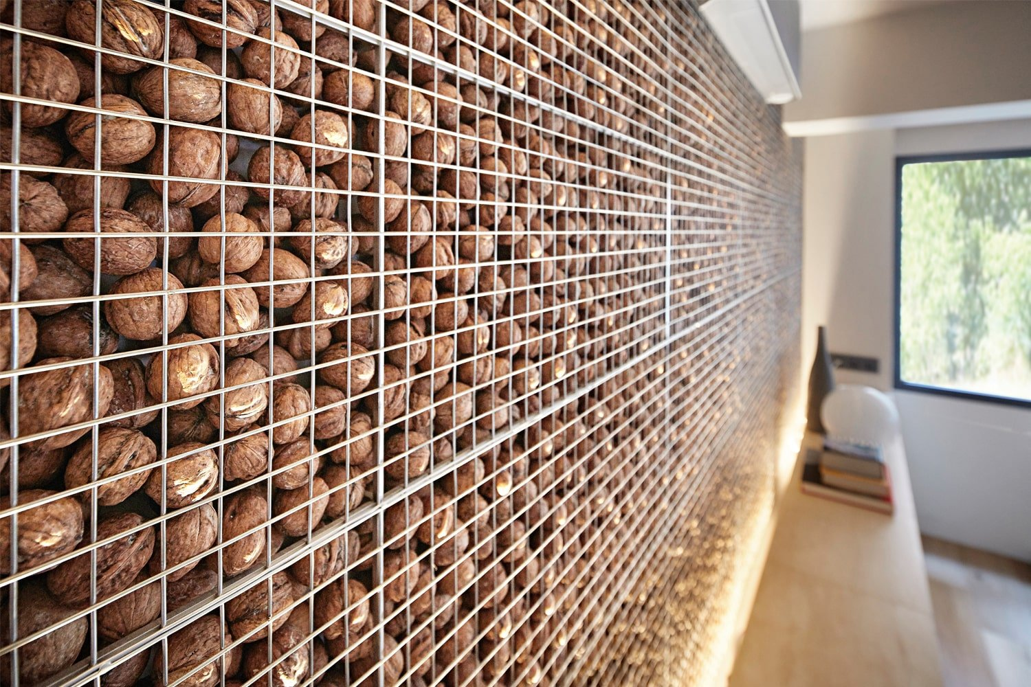 A closer look at the unique wall that adorns the sofa reveals that it is actually made of walnut shells inside a steel screen with lighting on its edges.